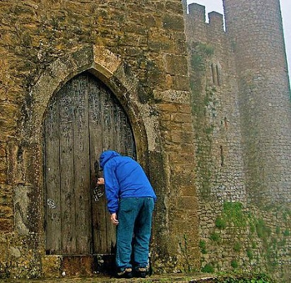 weary person knocking at old castle door